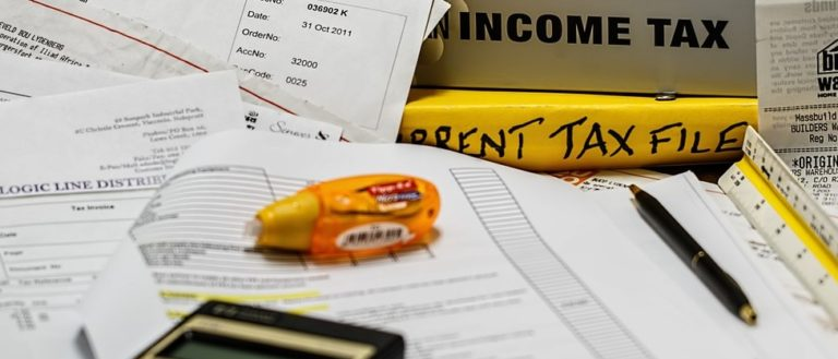 Tax documents and a calculator spread over a table.