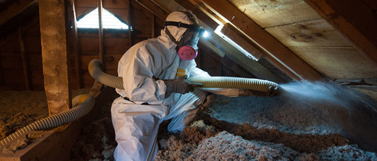 A worker spraying insulation in a home's attic.