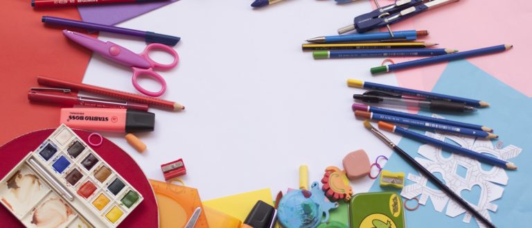 An assortment of school supplies on several pieces of construction paper.