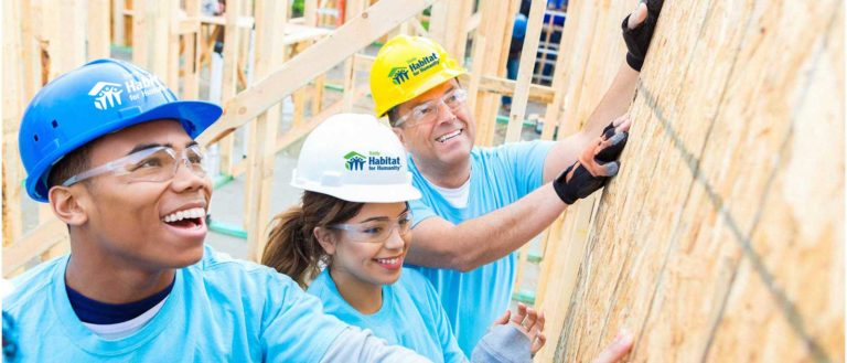 Habitat for Humanity workers placing wooden planks of a home.