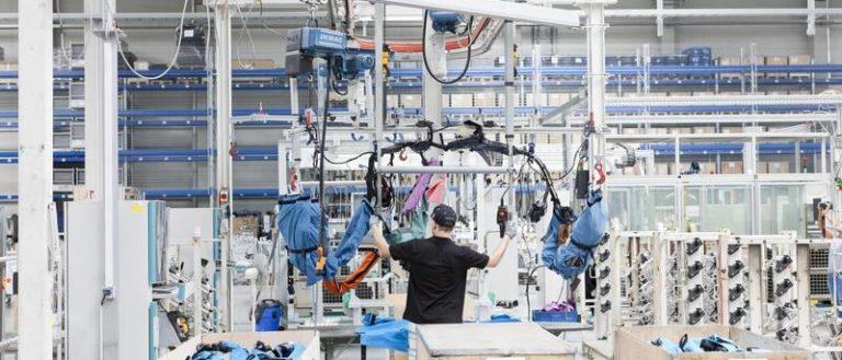 A Dräxlmaier worker assembling parts.