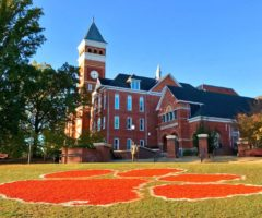 The orange Clemson logo on grass in front of a campus building.