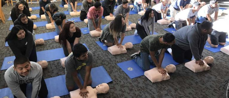 Students in school performing CPR compressions on a test dummy.
