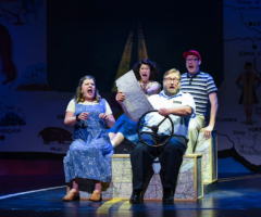 The cast of Greenville Theatre's Leaving Iowa driving an imaginary car on stage.