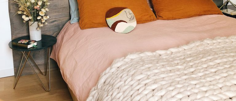 A bedroom mattress with pink sheets and orange pillows.