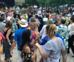 People dancing in downtown Greenville during a concert.