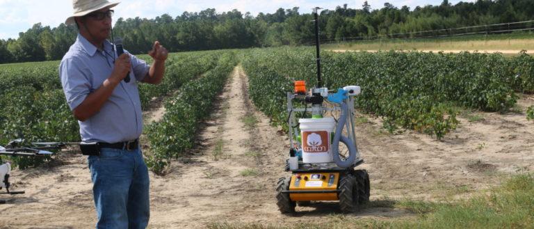 Joe Mari Maja alongside with a harvesting robot at a cotton farm.