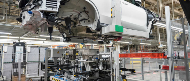 A BMW vehicle on an assembly line preparing for a hybrid battery insertion.